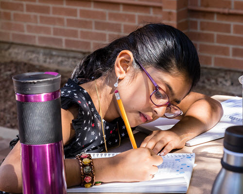 Image of a young girl writing in her journal outdoors during the 2018 Young Adult Writing Program. / Photo by Bruce Matsunaga