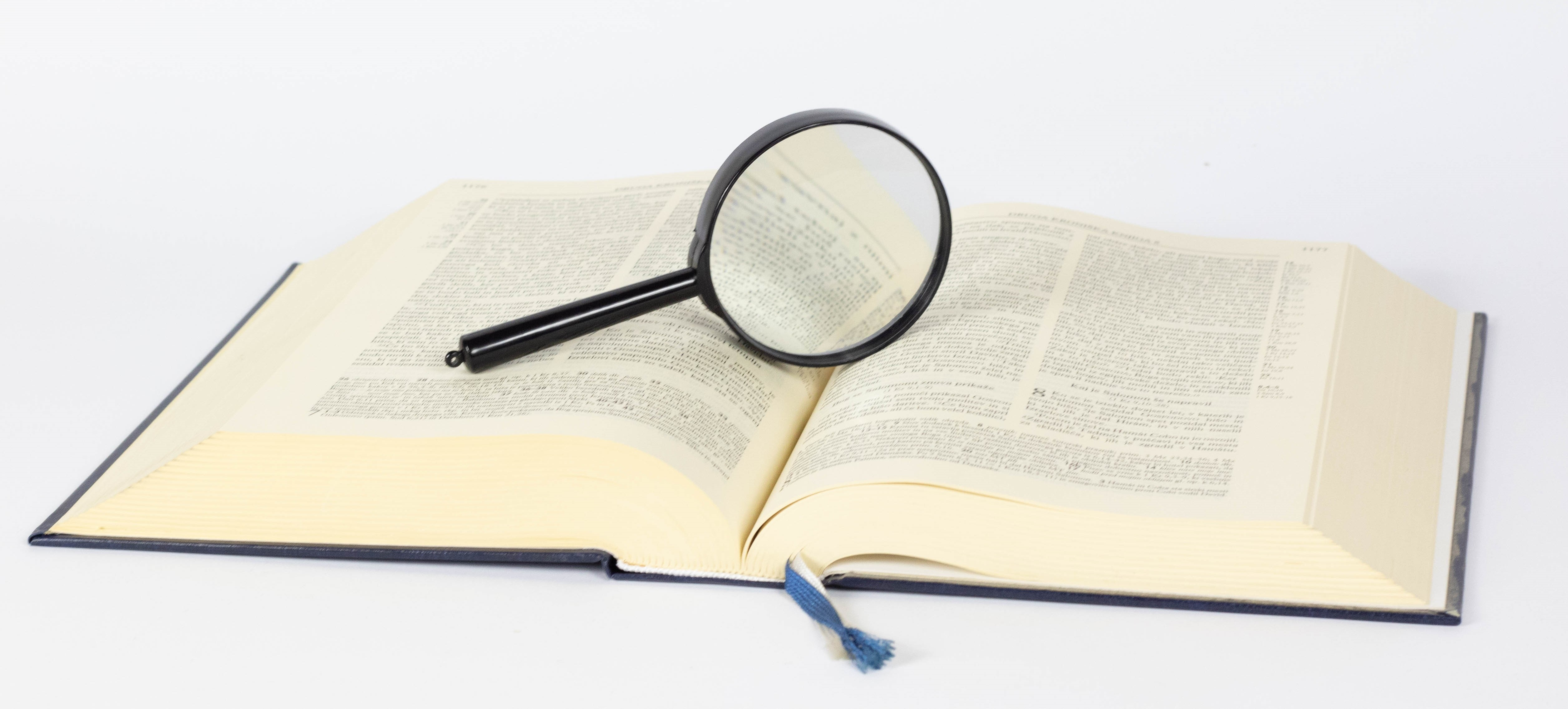 Image of a magnifying glass on a book / Photo by Marco Verch on Flickr