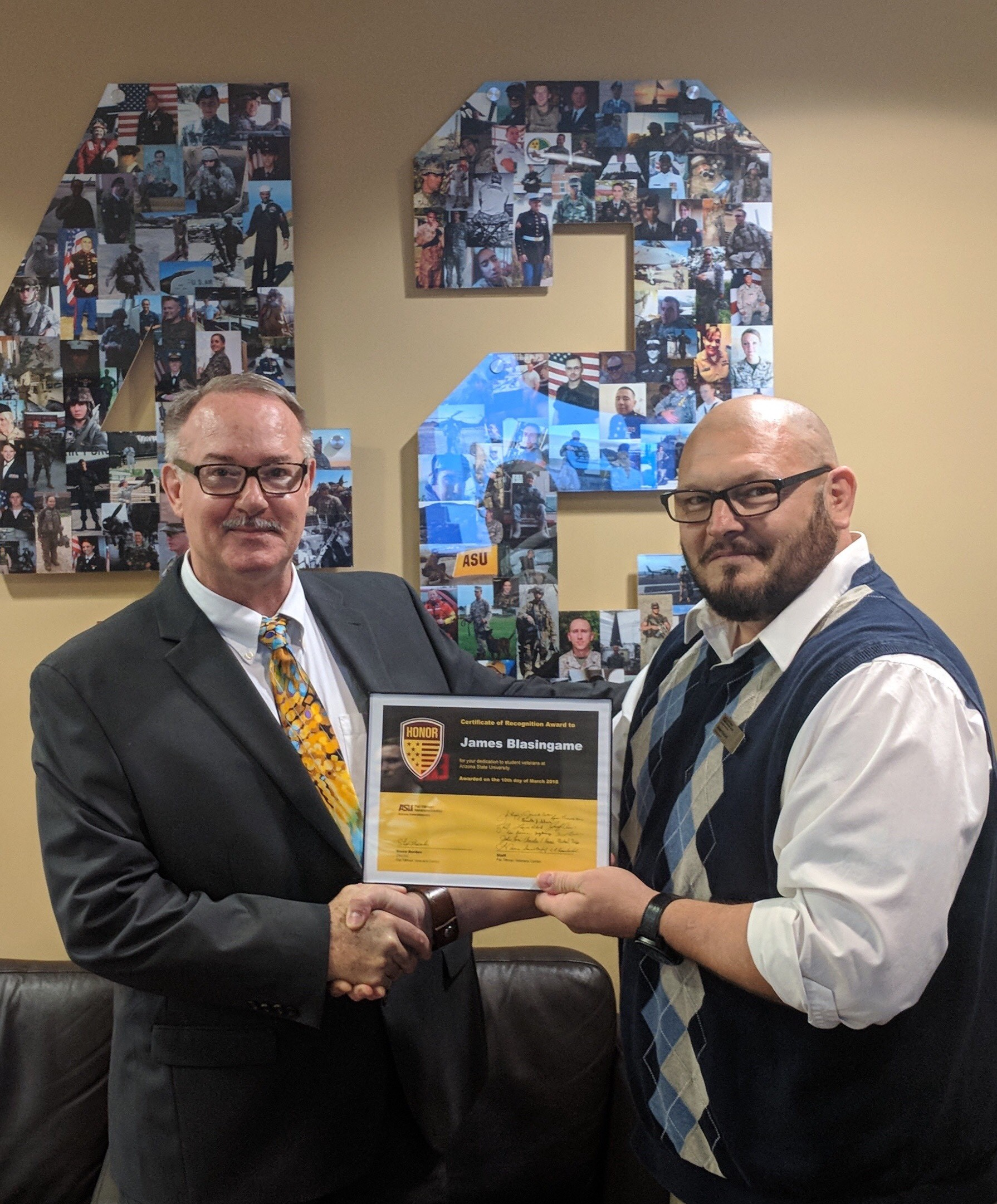Shawn Banzhaf, a military advocate at the ASU West campus, presents ASU professor James Blasingame with a Tillman Center Honor Roll Award.