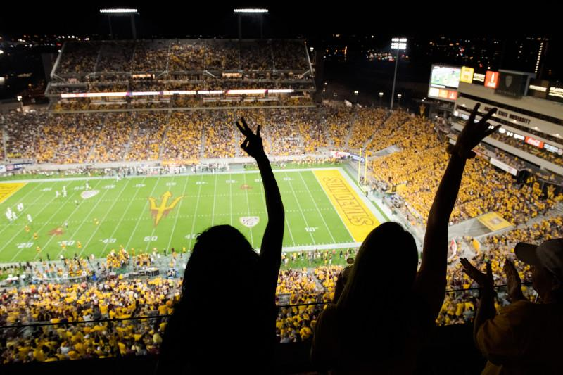 An image of two people making pitchfork salutes at an ASU football game. / Photo by Jarod Opperman
