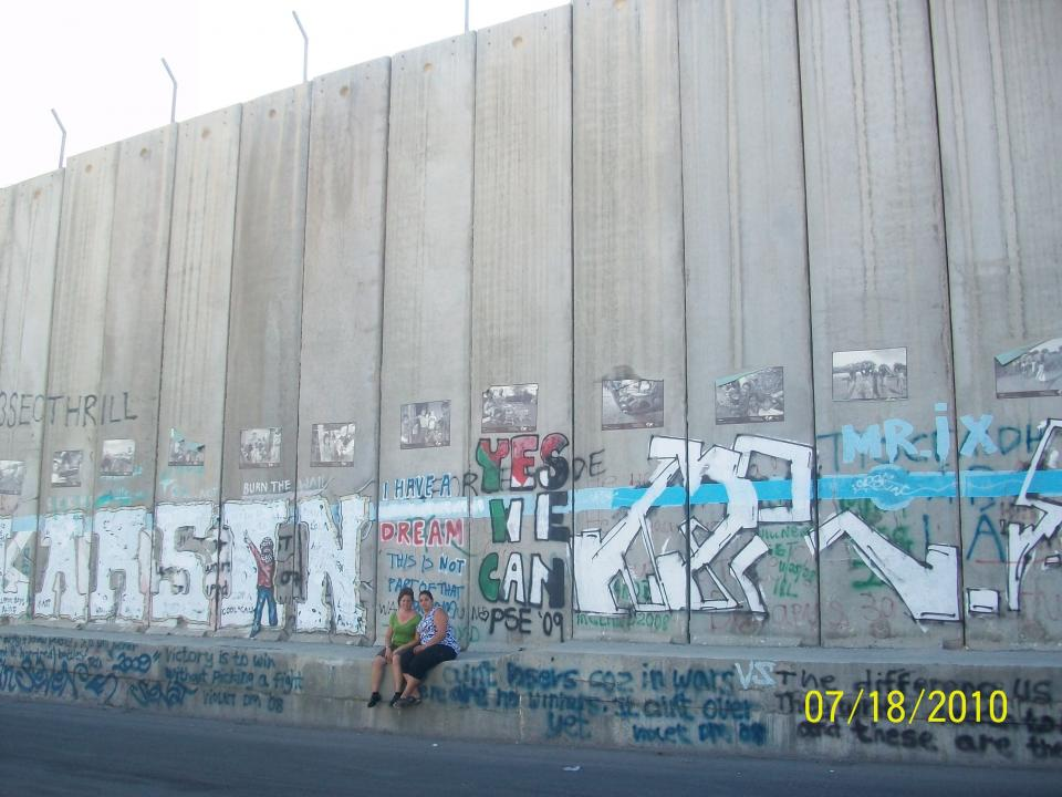 Sylvia Dahdal and her sister-in-law pose at the base of a section of the Separation Wall. / Courtesy photo