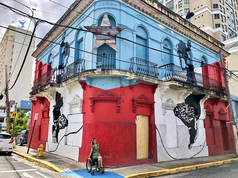 Edith Vélez Bermúdez poses near a building painted like Puerto Rico's flag. / Courtesy photo
