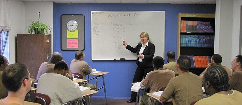 Image of a woman teaching a room of prison inmates / Photo Source: US Department of Justice, Bureau of Prisons