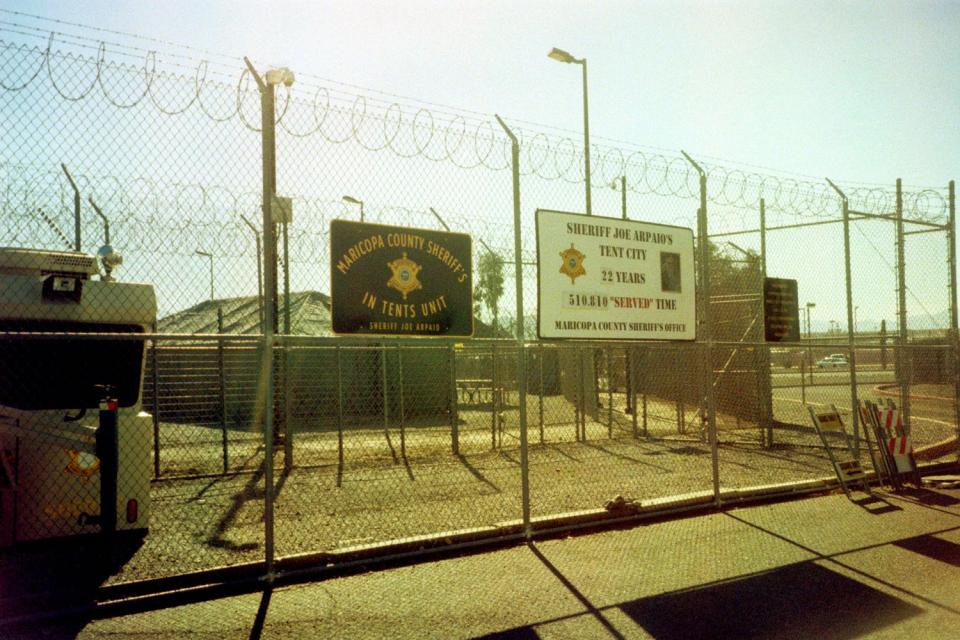 """A sign fence at Sheriff Joe Arpaio's infamous """"Tent City"""" in Arizona in 2016. Photo by ~filth~filler~ on Flickr. Used under CC 2.0."""