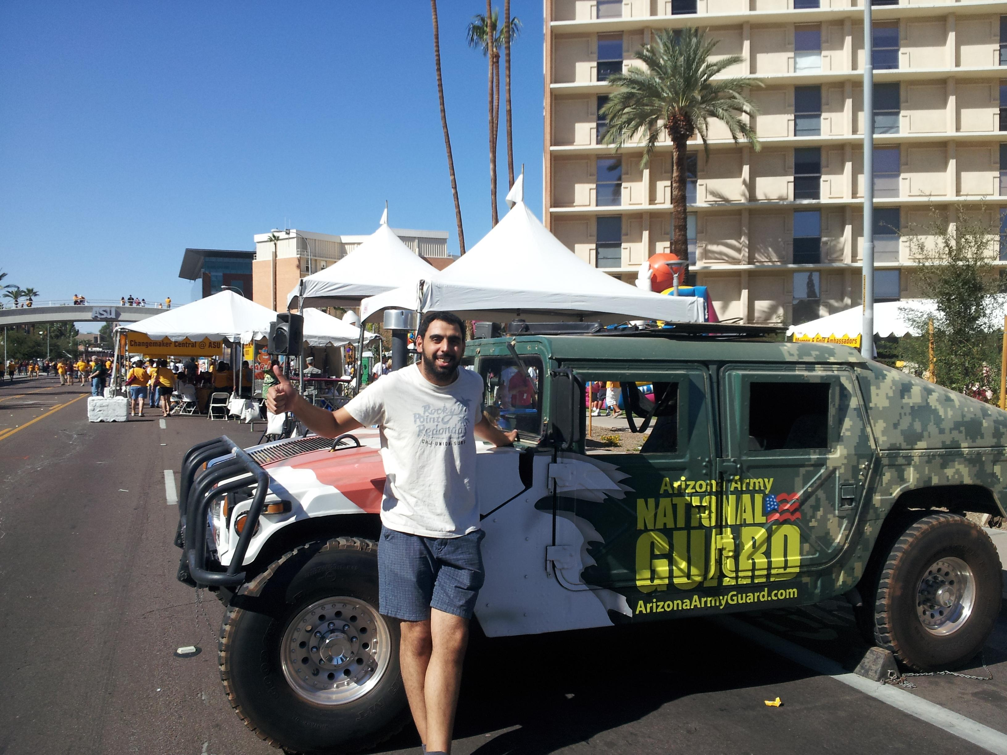 Abdelhamid Hamouda poses with an Arizona Army National Guard vehicle at ASU's Homecoming Parade and Block Party in October 2012.